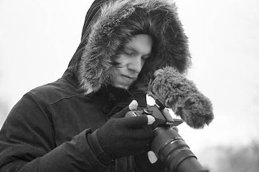 A man using a Nikon d5100 camera outside in the cold