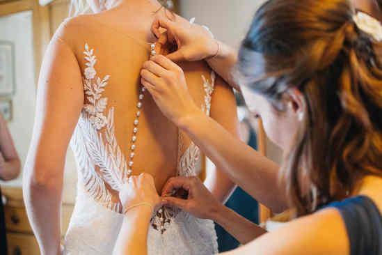 bridesmaids fastening wedding dress