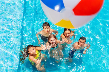Many kids in swimming pool play with inf