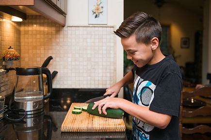 Young boy helping in kitchen