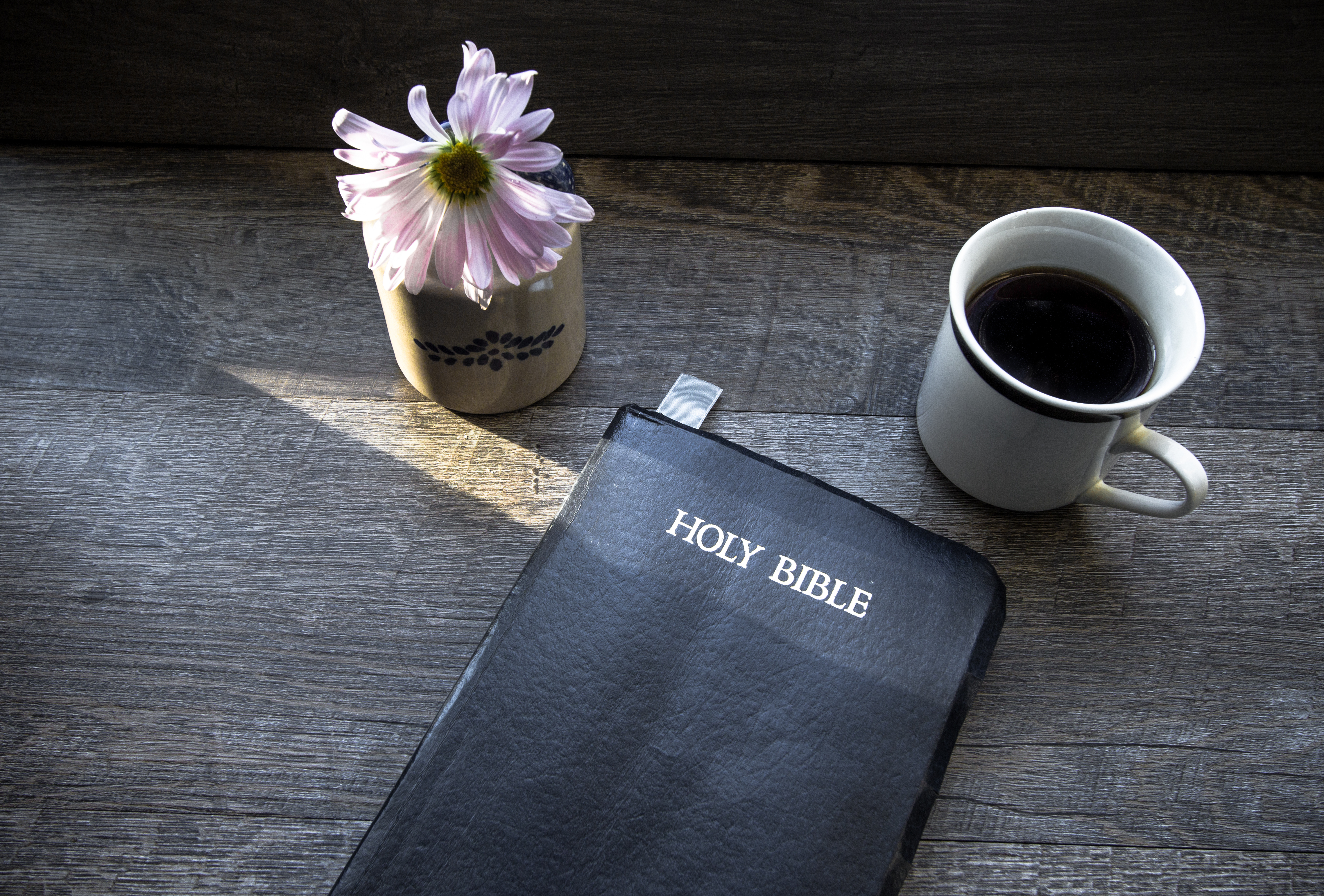 Morning Coffee With Bible Illuminated By Sunlight. Cup of coffee with Christian Bible illuminated by