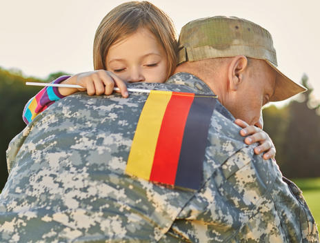 Happy reunion of german family. Little girl with deutsch flag is hugging her father._edite