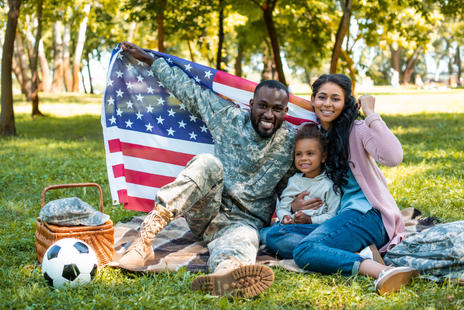 happy african american soldier in military uniform and family holding american flag in par
