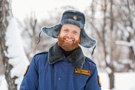 Russian military with a red beard and mustache in a winter blue uniform with the inscripti
