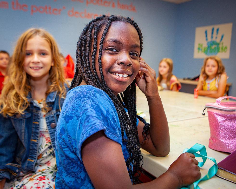 Elementary school children smiling in a Bible school classroom.