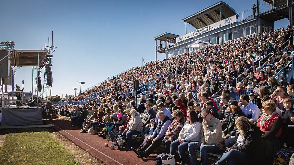 Crowd of North Boulevard's entire congregation filling the bleachers of a soccer stadium at an All-Campus event. David Young preaches from a stage set up on the field.
