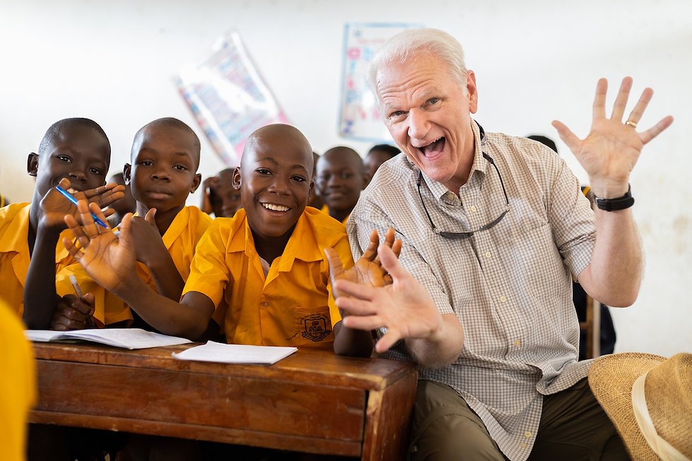 """Elder making """"jazz hands"""" and smiling big as he sits next to elementary students in Africa."""
