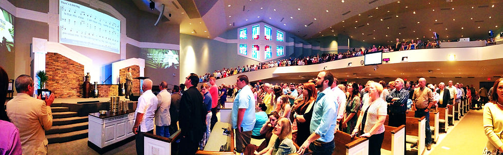 Side view of East Campus Auditorium with a ground level and balcony full of people standing and singing songs of praise.