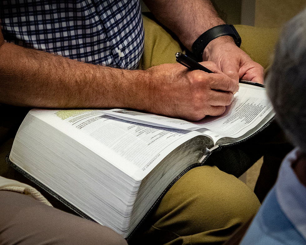 A man's hand taking notes with his Bible open in his lap.