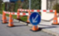 Panneau de signalisation temporaire avec llisses et cônes.