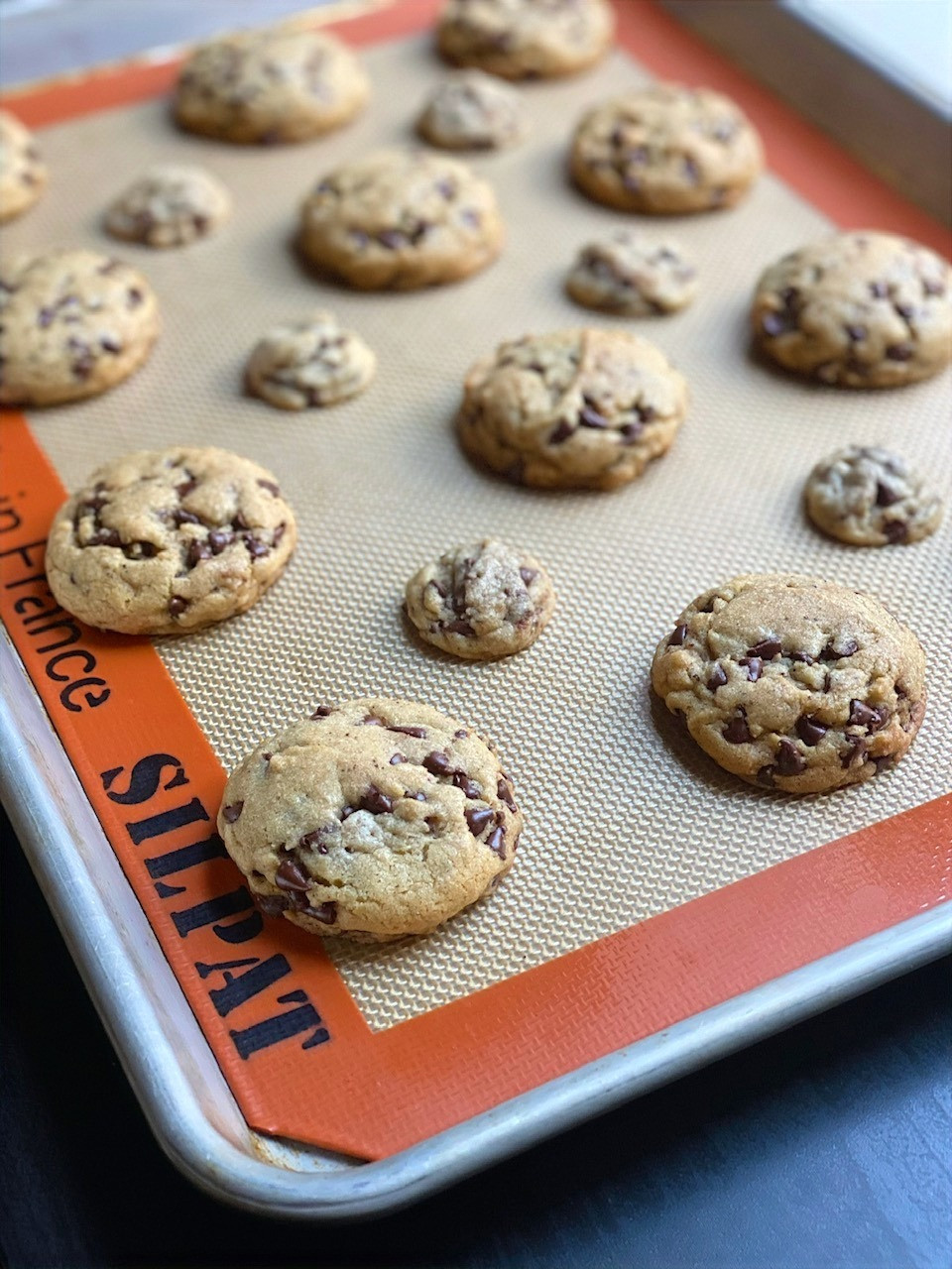 chocolate chip cookies on a nordicware baking sheet featuring a silpat nonstick baking mat