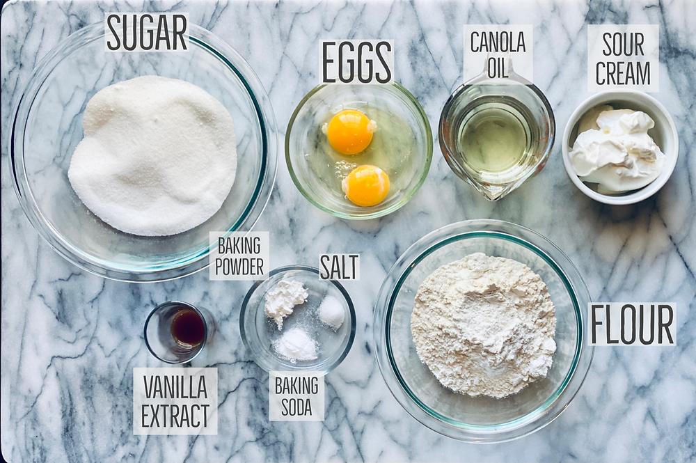 ingredients for Vanilla cupcakes including sugar, flour, eggs, canola oil, sour cream, baking powder, vanilla extract, baking soda, salt, canola oil