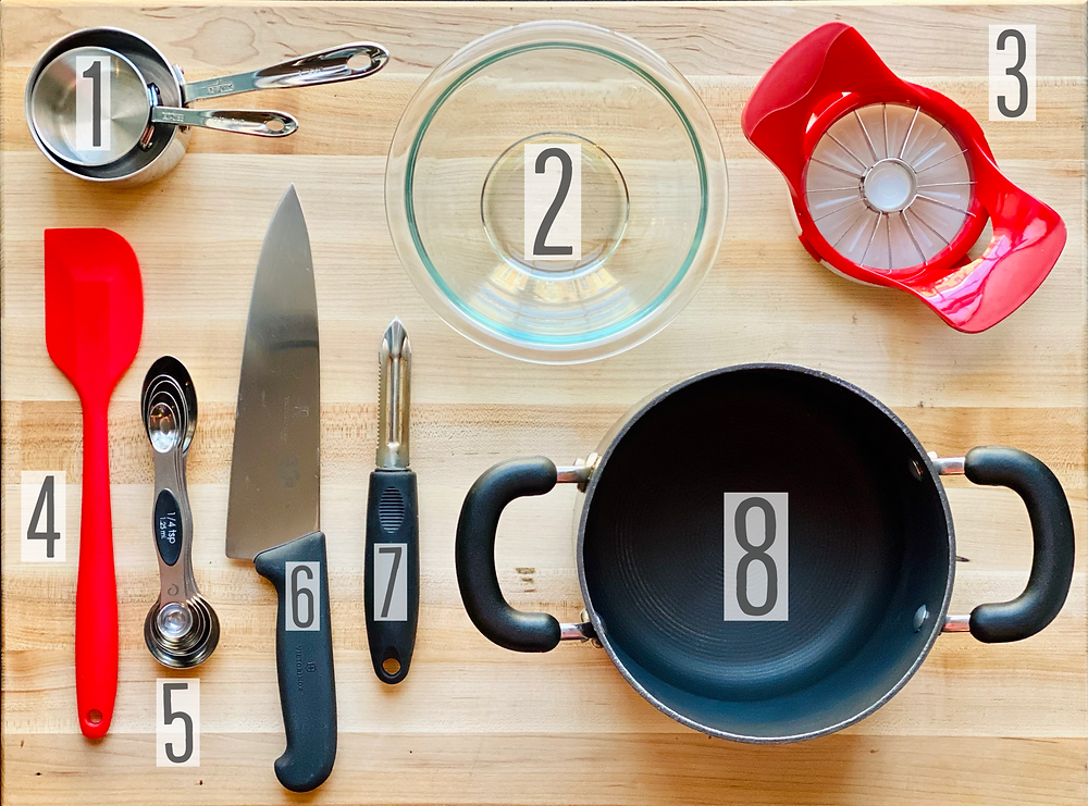 kitchen utensils and equipment from Desserts Capital delivery based online bakeshop in Philadelphia, Pennsylvania, used to prepare cream cheese apple danish which includes measuring cups for dry ingredients, pyrex mixing bowl, apple slicer/corer, silicone spatula, magnetic measuring spoons set, victorinox chefs knife, vegetable/fruit peeler and medium sized saucepan