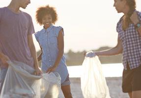 ボランティアがビーチにゴミを集める