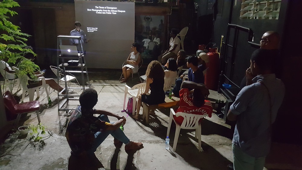 "A section of the audience on the night of Emilie Boone's presentation ""The terms of emergence: How photography from the African diaspora came into public view,"" held at Alice Yard, Woodbrook"