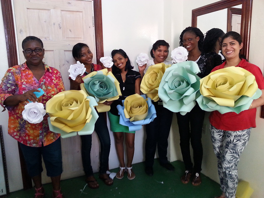 A group of satisfied participants after completing one of Innovign's paper flower workshops