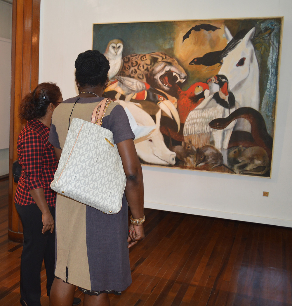 """Throwback: Patrons viewing an Aubrey Williams painting in the """"Circa 1970: The Crossroads"""" exhibition which opened in February of 2016 at the National Gallery of Art, Castellani House."""