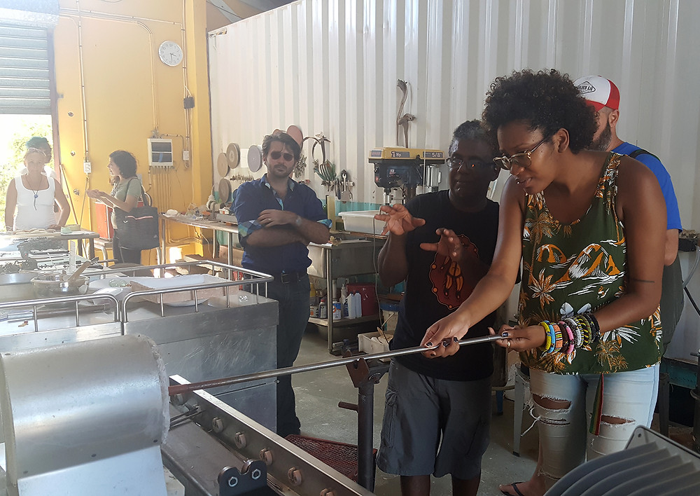 Ciro Abath demonstrates glass blowing techniques with the help of Shanice Smith (Barbados) during a trip to his studio