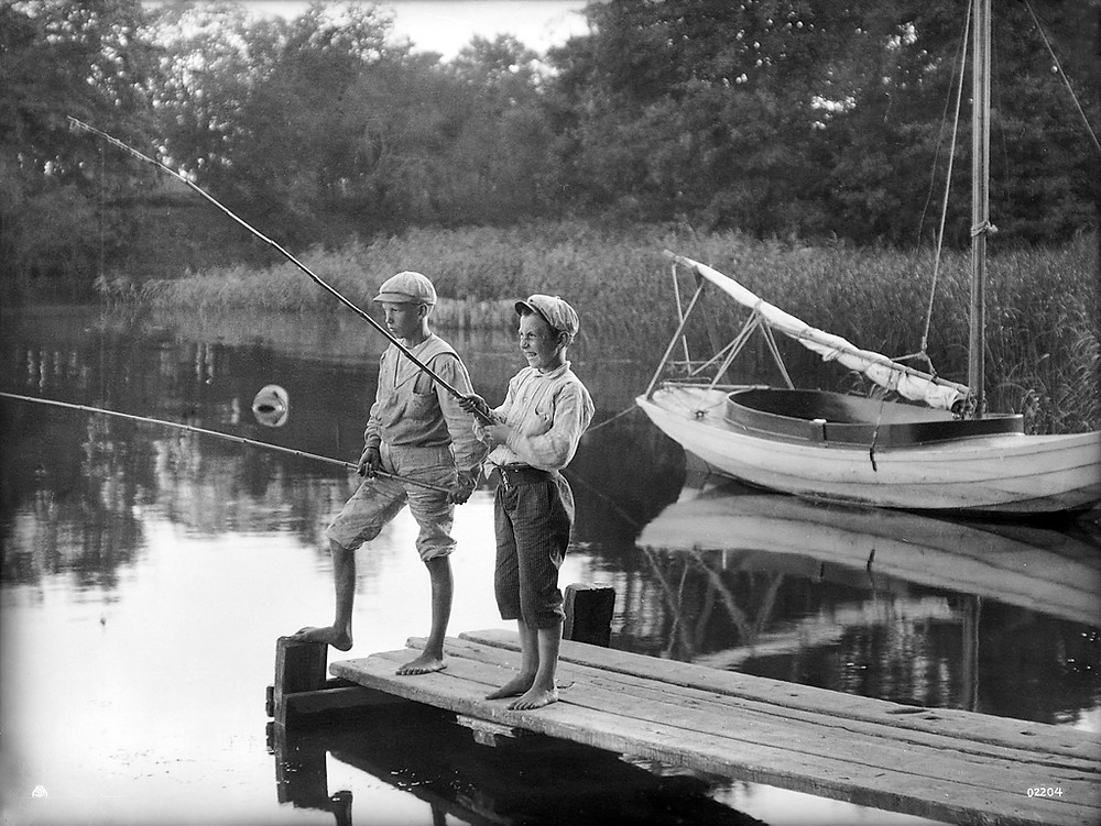 Two boys fishing, somewhere in Sweden. In the background a sailing boat.