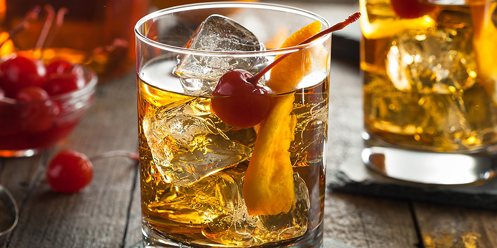 An Old Fashioned cocktail with ice cubes and a cherry in a vintage whiskey glass