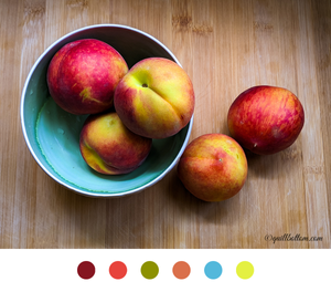 Image of a bowl of peaches with swatches of color beneath it. (Brick red, coral, sage, peach, sky blue and yellow green)