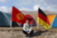 Nurzat Kleefeld sitzt vor drei Zelten mit Deutschland Fahne und Kirgistan Fahne