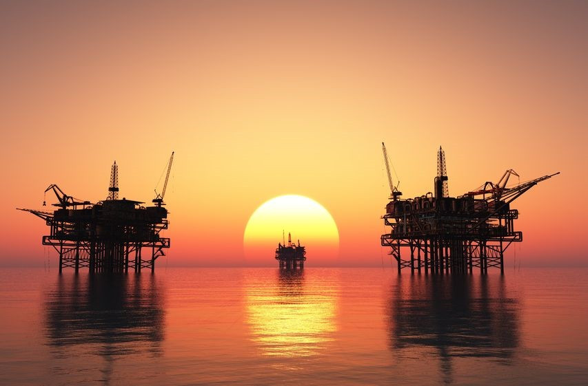 Oil platform in middle of sea at sunset