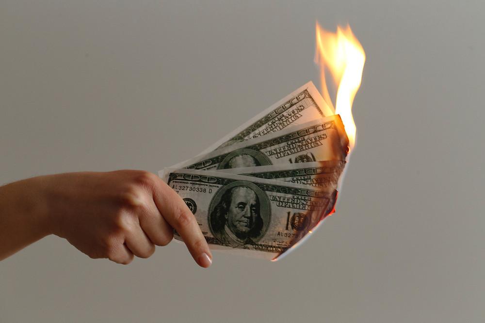 Man burning one hundred dollar bills