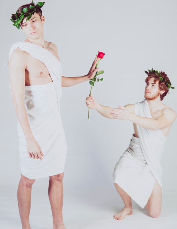 """alt=""""man in white toga refusing rose from another man"""""""