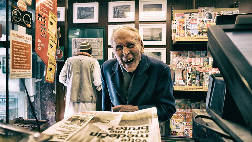 Crazy Man Laughing over old newspaper