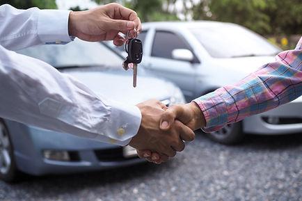 car-salesman-is-handing-keys-buyer-after