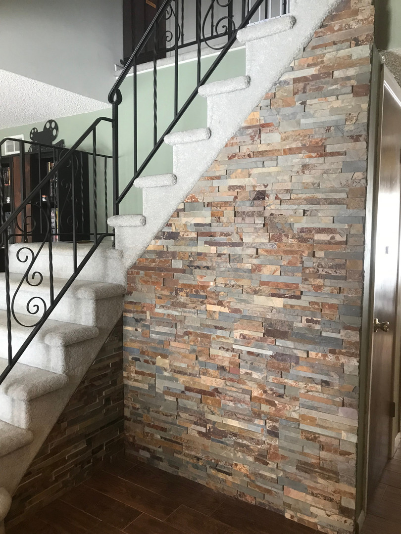 Stone veneer applied to wall under stairs