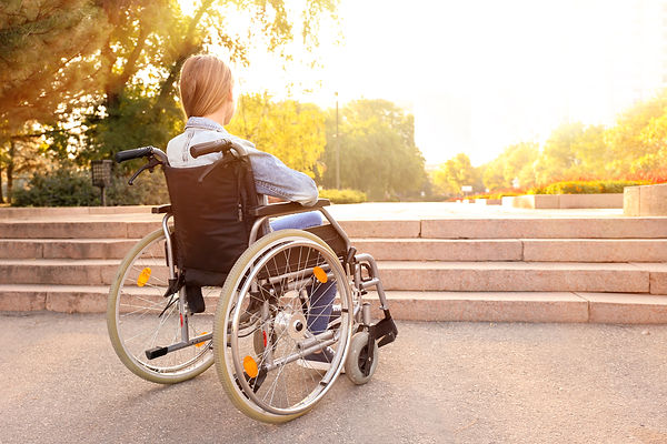 Girl in wheelchair near stairs outdoors.