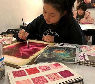 Art student in class painting in her sketchbook