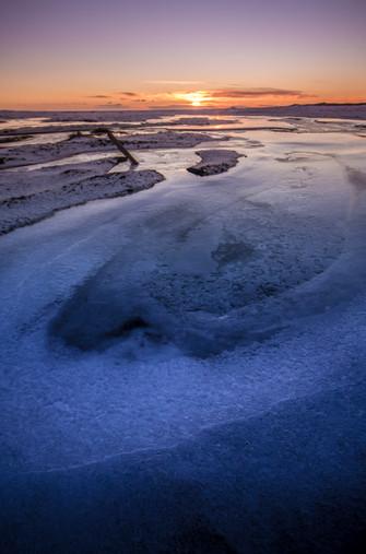 Looking towards sunset on a frozen beach of black sand.