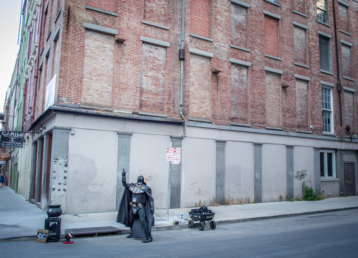 A street performer dressed as Darth Vader points to the sky in New Orleans