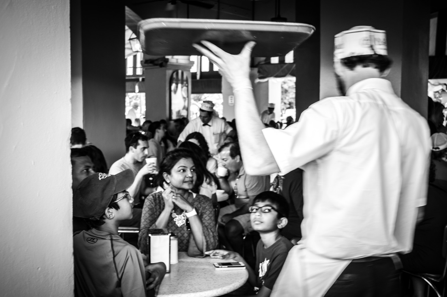 A family eagerly welcomes their long-awaited beignets at Cafe Du Monde in New Orleans