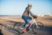Woman riding bike at beach
