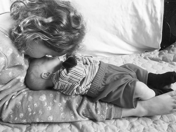 Older sister kissing her baby brother