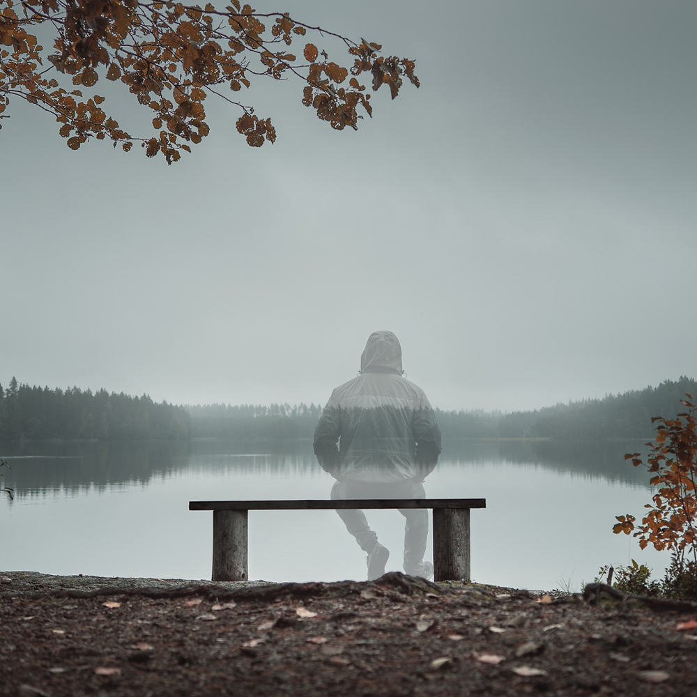Picture of someone sitting on a bench and the person is transparent, almost invisible