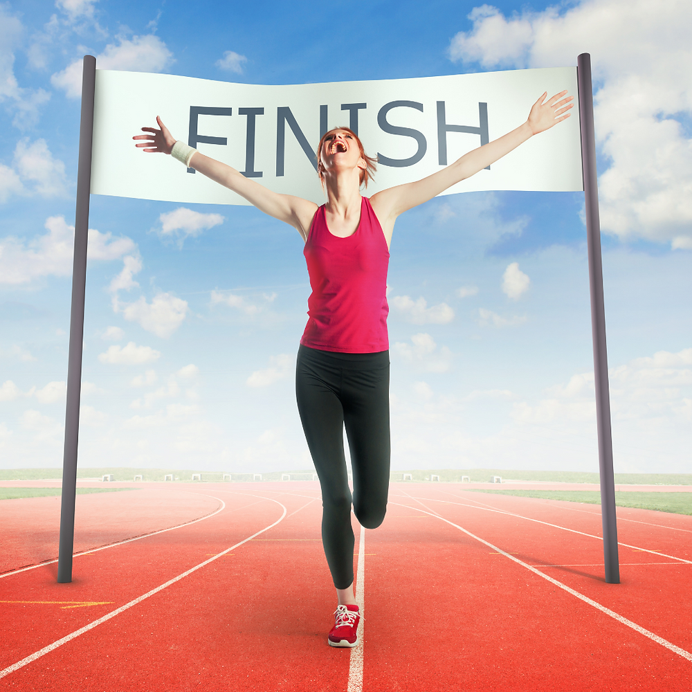 A picture of a women with arms stretched out wide running through a finish line after a race.
