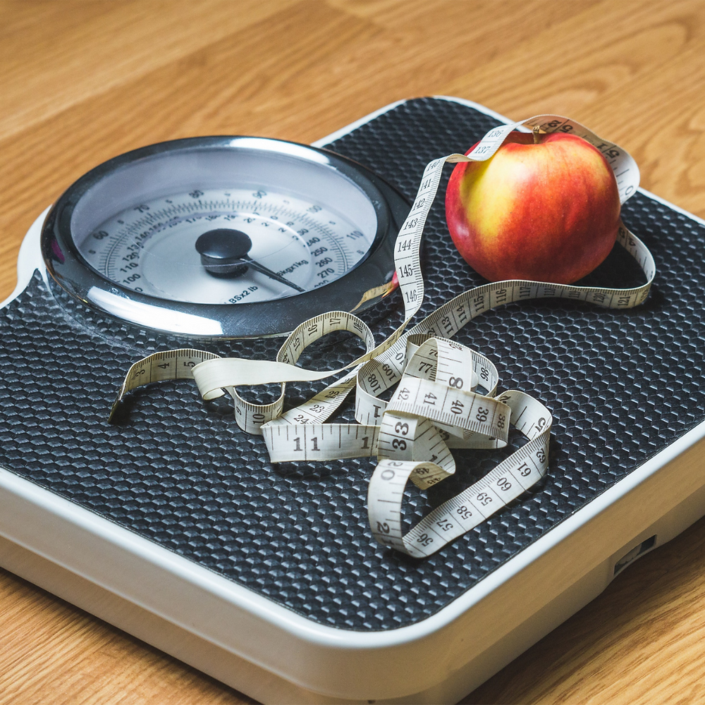 Picture of a weight scale with a tape measure and apple setting on top of it