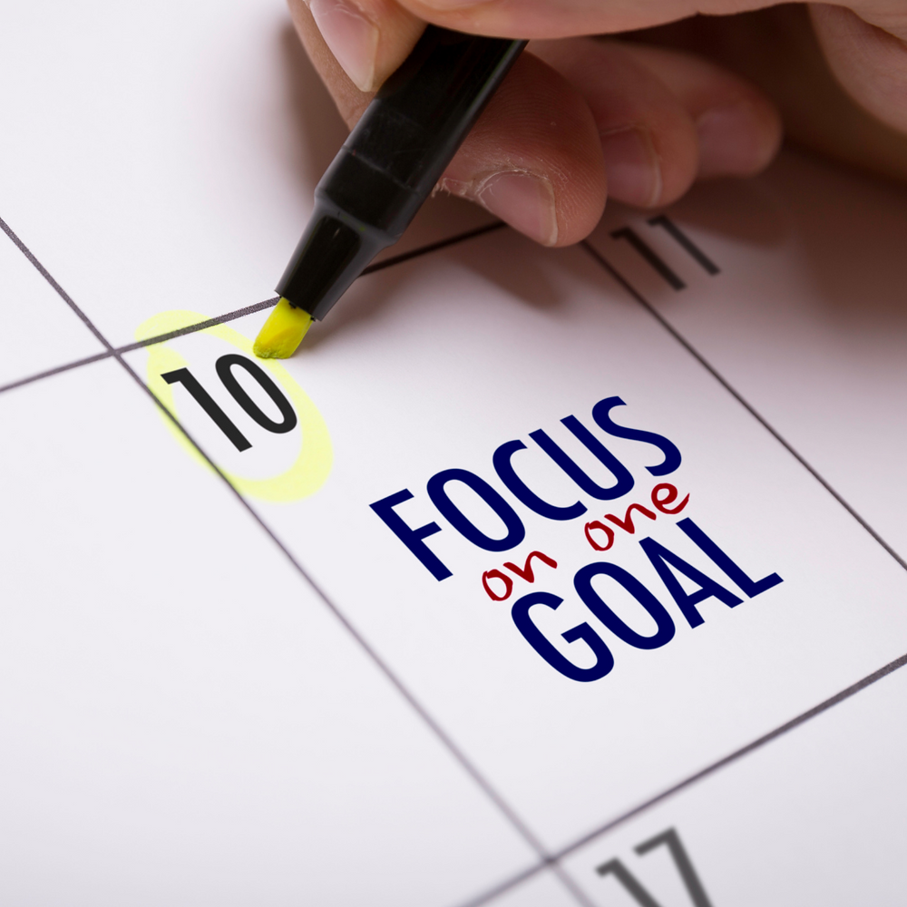 A picture of the 10th day of a calendar.  A person is circling the number 10.  The words on the calendar say Focus on one Goal