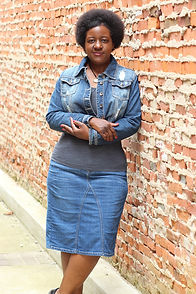 Gwen Alexander leaning against a brick wall looking forward