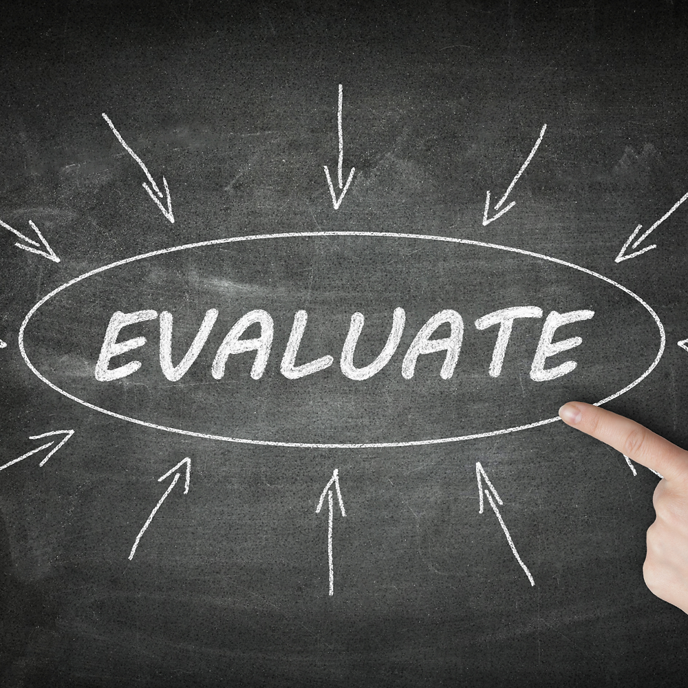 A picture of a chalk board with the word Evaluate written on it.  There is an index finger pointing at the word.