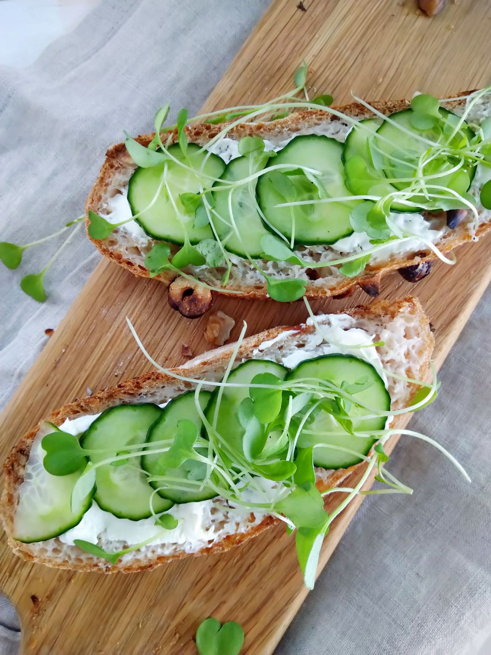 Gluten-free bread with cream cheese, cucumber slices and sprouts.