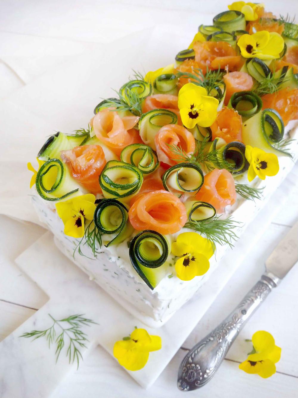 Juhlavan lohivoileipäkakun koristelu kylmäsavulohella, kesäkurpitsalla, yrteillä ja syötävillä kukilla. Kaunis kukka sopii kakun koristeeksi. Hyvä lohitäyte ja kasvipohjainen tuorejuusto. Herkullinen lohikakku. Lämminsavulohi, graavilohi ja kylmäsavulohi resepti. Terveellinen lohi. Kaunis voileipäkakku. Maidoton ja gluteeniton juhlava voileipäkakku. Lohi koristelu. Lohivoileipäkakku 9 hengelle.