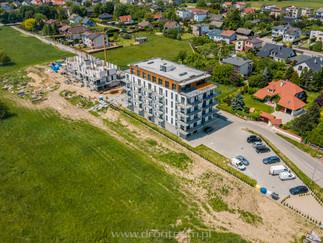 Pierwszy budynek został odebrany, a lokatorzy już mieszkają. Gratulacje! Zielone Tarasy Kęty etap 1 został ukończony. Zdjęcie z powietrza przedstawia inwestycję wraz z parkingiem i drugim budynkiem w tle.