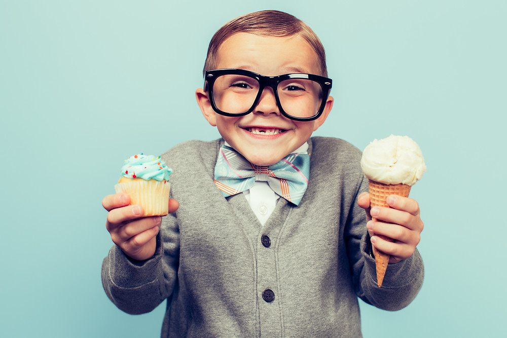 Boy with glasses holding cake and ice cream