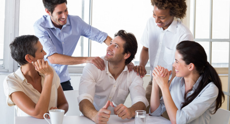 Man looking up smiling as team mates surround and praise him